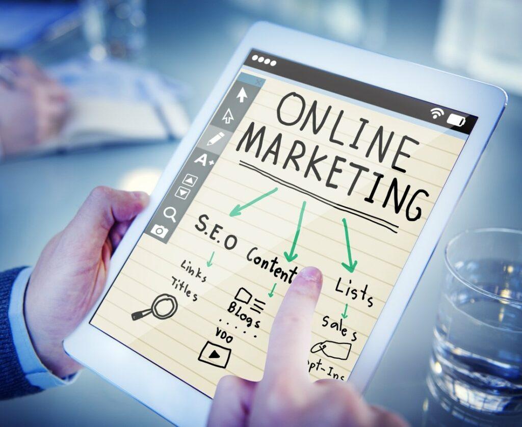 mão apontando para iPad que mostra Online Marketing e fluxograma para SEO, Conteúdo e Listas