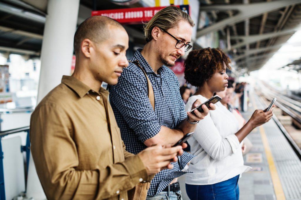 três pessoas em pé cada uma olhando seu smartphone